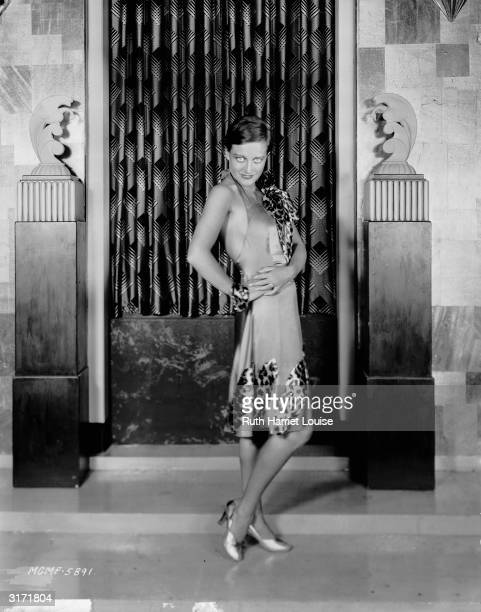 Film star Joan Crawford in a short sleeveless dress with leopard print trim
