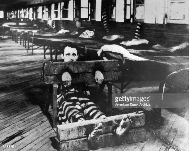 A prisoner in a striped uniform sits with arms and legs in stockades on a wooden slatted floor in front of a row of cots Spalding County Chain Gang...