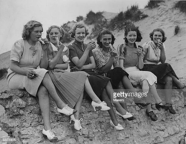 A happy party of pretty holidaymakers enjoying an ice cream on a seawall at Porthcawl Wales