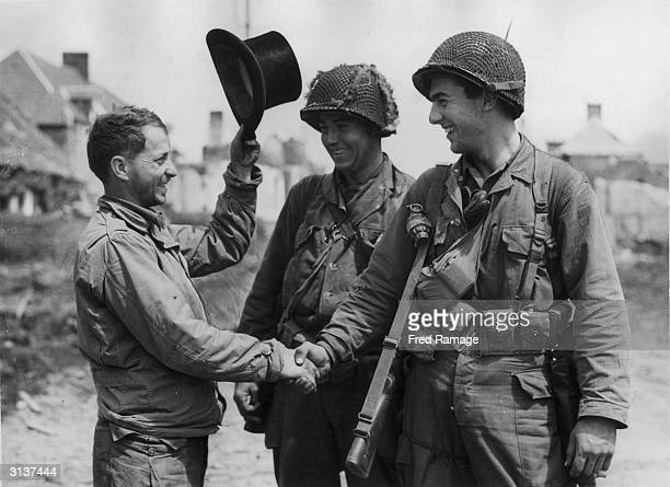 Private Philip Wiley of Iowa greets his comrades who have just returned from the front line Private James Buckley of Buffalo, New York, and Private...