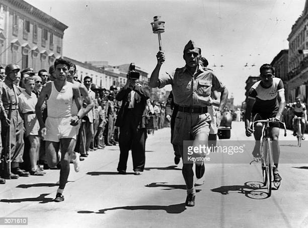 The Olympic flame carried by an Italian cadet through the streets of Bari on its way to London for the opening ceremony