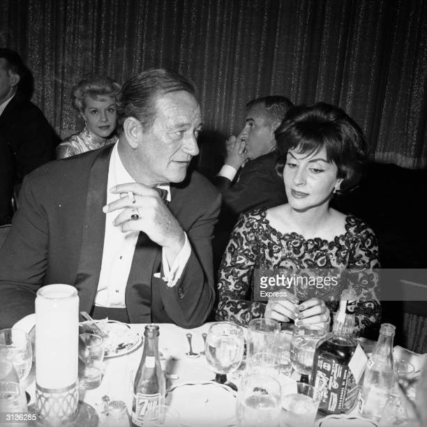 American actor John Wayne with his wife Pilar Palette at the Cocoanut Grove club in Hollywood