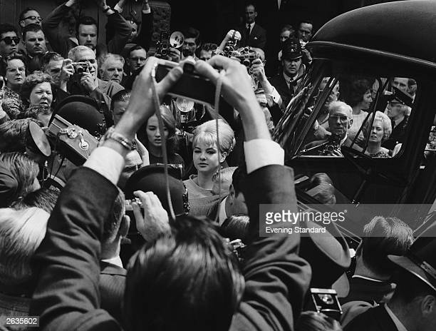Models and showgirls Mandy RiceDavies and Christine Keeler surrounded by press photographers as they leave the Old Bailey during the trial of Dr...