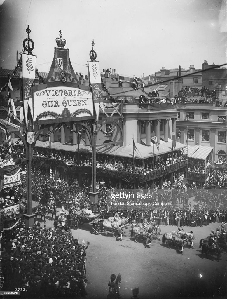 Queen Victoria's carriage in the procession from Westminster Abbey, London, celebrating her Golden Jubilee. Crowds line the streets, balconies and roofs overlooking the route.