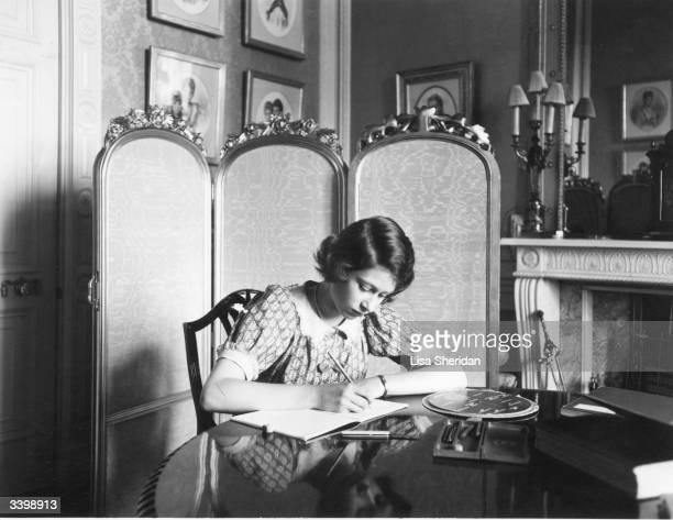 Princess Elizabeth working on her studies at a desk in Windsor Castle.