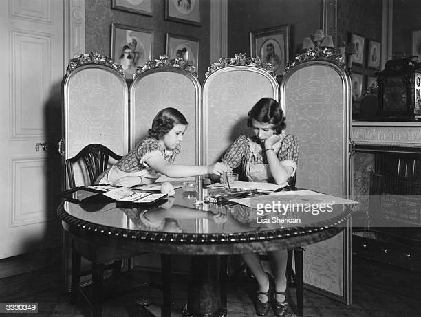 Princess Margaret Rose and Princess Elizabeth working on paintings in the school room of Buckingham Palace London