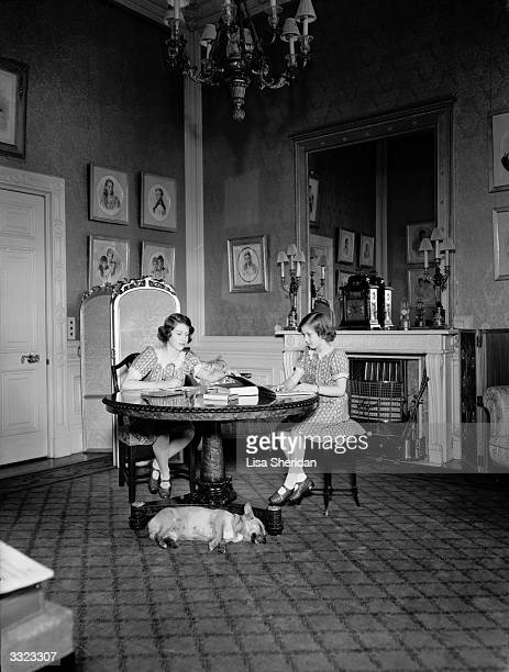 Princesses Elizabeth and Margaret studying whilst a corgi dog sleeps at their feet in a drawing room at Windsor Castle Berkshire