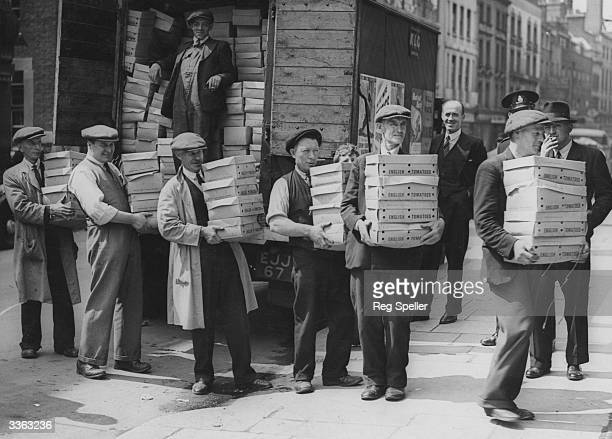 Unloading a large consignment of tomatoes at Covent Garden Market London