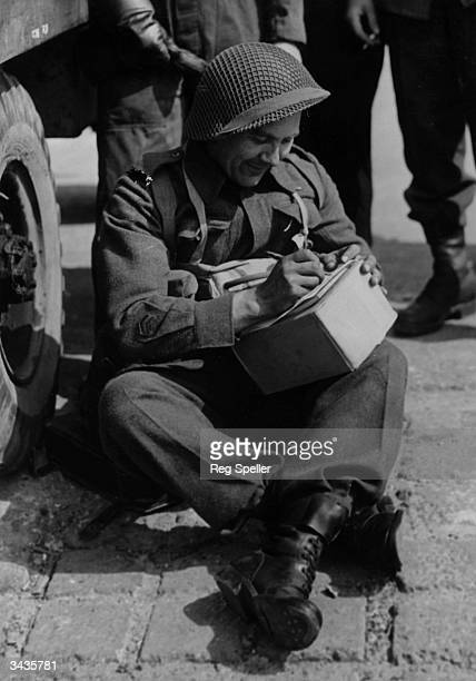 A Canadian artillery man writing a letter before leaving England for France