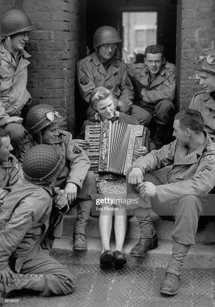 Mrs M Hale, whose husband is fighting in France, spends the day giving troops tea and refreshments in the road before her house, and entertaining them with accordion music.