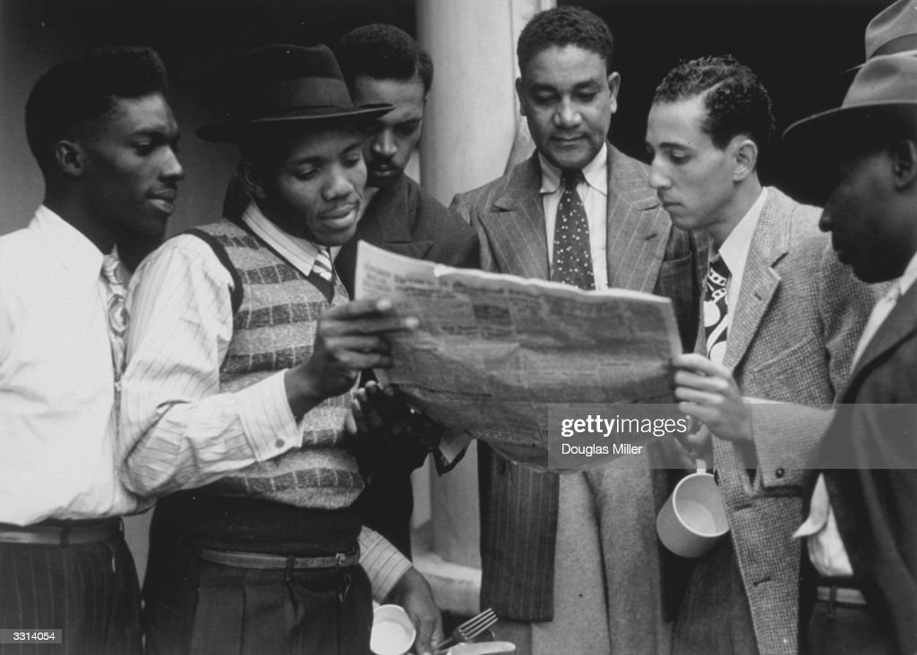 Jamaicans reading a newspaper whilst on board the ex-troopship 'Empire Windrush' bound for Tilbury docks in Essex.