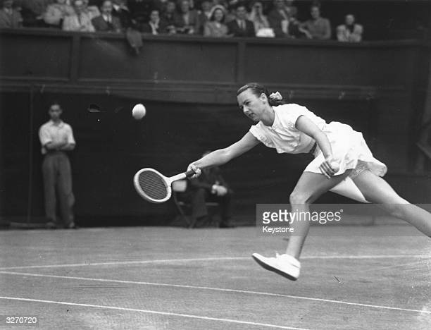 American tennis player Gertrude 'Gussie' Moran or Gorgeous Gussie stretches for the ball during her match against E M Wilford of Great Britain at...