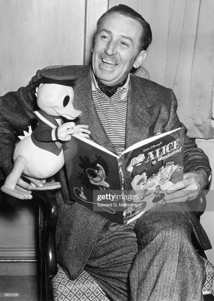 Creator of Mickey Mouse Walt Disney (1901-1966) arrives in London to see the premiere of his latest film. He holds a model of his character Donald Duck whilst looking at a copy of the Walt Disney book of the new film 'Alice In Wonderland'.