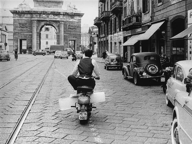 A man carrying a block of ice home on his scooter in...