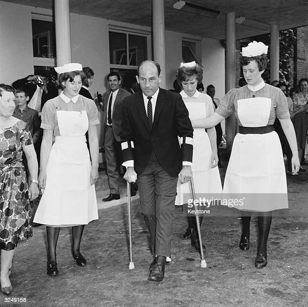 Stirling Moss the British racing driver leaving Atkinson Morley's Hospital in Wimbledon after recovering from an accident at a Goodwood race