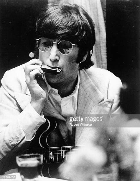 Beatles singer songwriter and guitarist John Lennon plays the harmonica his guitar rested on his knee