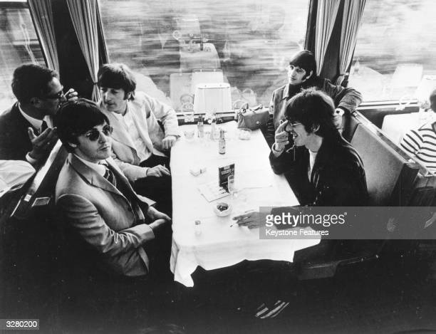 The Beatles relax in the buffet car of a train during a tour of Europe