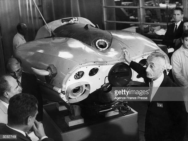 French underwater explorer Jacques Cousteau explains the workings of the 'Sea Flea' a oneman research submarine capable of diving 500 meters to...