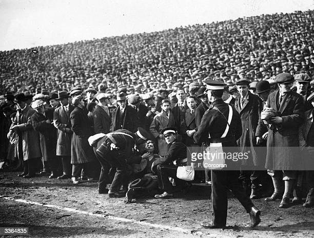 A woman who has fainted receives medical attention on the pitch sidelines during the FA Cup SemiFinal between Sheffield Wednesday and Huddersfield...