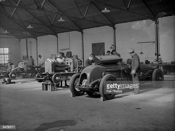 Mechanics at work on the bodies of three Bentley race cars at a garage in Welwyn Hertfordshire