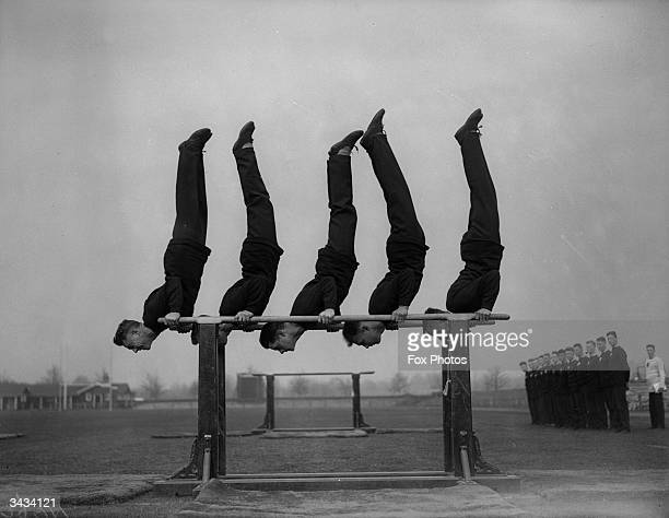 Soldiers doing handstands on parallel bars at the Army Physical Training School, Aldershot, Hampshire.