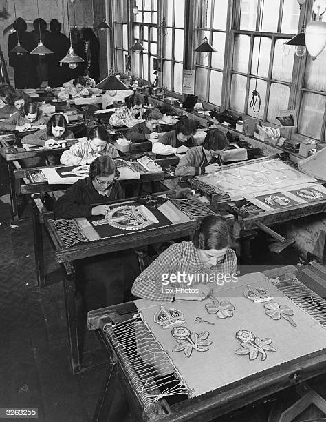 Women at work on sections of the King's own Standard which will be presented by the King to the Grenadier Guards on the occasion of his coronation...
