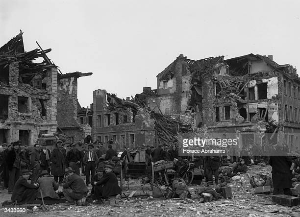 Citizens of Saarbrucken in southwest Germany congregate in the ruined city square with their belongings The city fell without a battle to the...