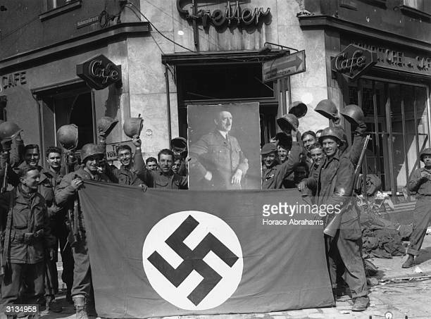 Soldiers of the 70th division of the American 7th Army hold up a Nazi flag and a portrait of Adolf Hitler taken during the World War II capture of...