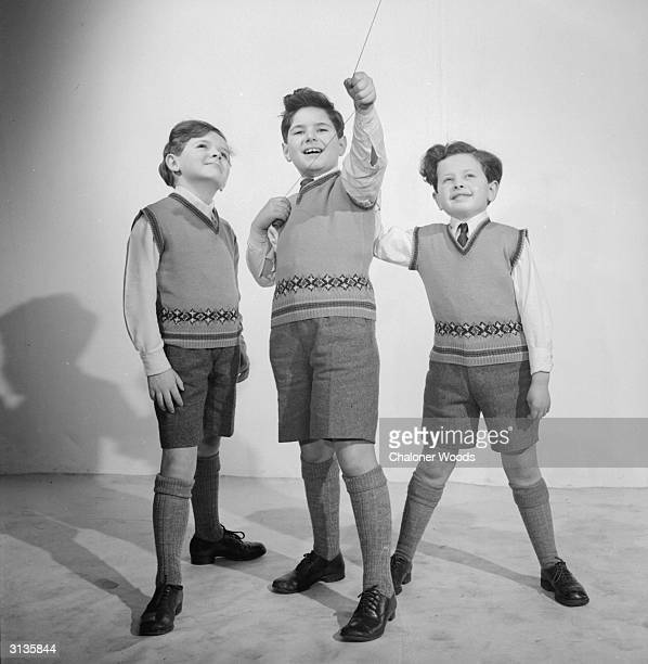 Three boys model pullovers with dropped shoulder line and a line of fairisle patterning round the waist
