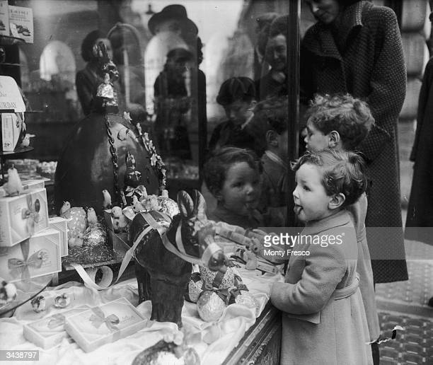 A little boy finds it hard to contain his excitement at a giant Easter egg display in a sweet shop on London's Regent Street
