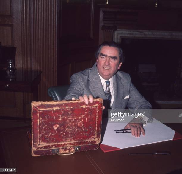 British Labour politician and Chancellor of The Exchequer Denis Healey opening the budget box in which the papers for the budget speech are carried...
