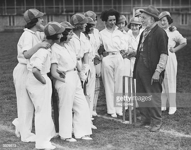 Elderly hay-cutter Mr Wright gives a few words of advice to the Rego Ladies Cricket team during their practice session at Edmonton.