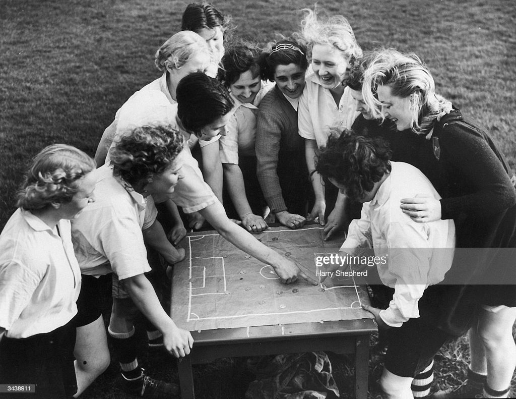 Members of the Preston Ladies Football Club listen to their captain, Miss Parr, as she discusses tactics with the aid of a cloth pitch diagram. They are about to embark on a tour of Scotland and also have a match with the international Belgian Ladies team to train for.