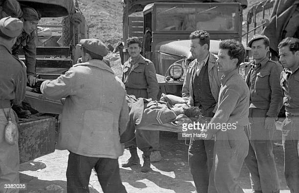 A group of soldiers loading a wounded man on a stretcher into a van during the Greek Civil War Original Publication Picture Post 4551 The War For...