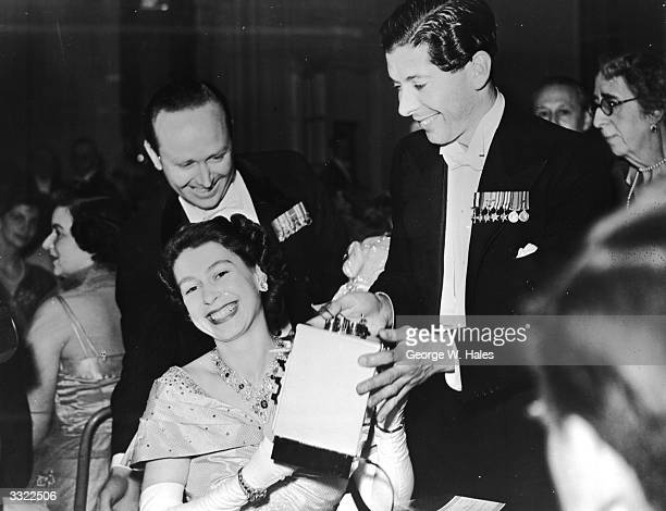 Princess Elizabeth being presented with a toy cooking stove for Prince Charles by the Hon Piers St Aubyn during a flower Ball at the Savoy Hotel...
