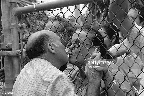 A tender kiss stolen through a steel fence after fifteen years of separation she a Cuban exile who fled the Castro regime in 1965 and he a Mariel...