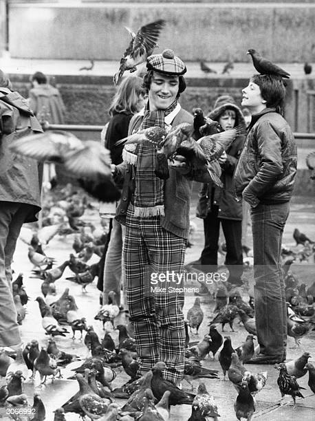 Clad in tartan, a Scottish football supporter feeds the pigeons in Trafalgar Square, London. He is down south for an England versus Scotland match.