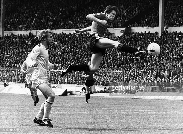 Queens Park Rangers footballer Gary Waddock executes a flying kick watched by Tottenham Hotspur's Steve Archibald in the 1982 FA Cup final at Wembley...