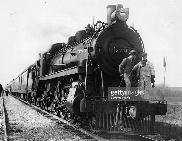 The Prince of Wales chatting to the engine driver on the cowcatcher of his locomotive during the Prince's Canadian tour