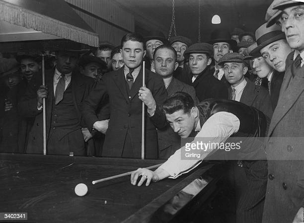 Middleweight champion Len Harvey plays a shot in a game of billiards while bantamweight champion Teddy Baldock looks on