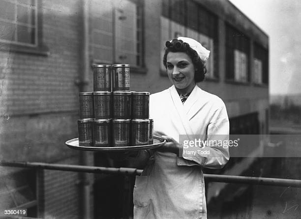 Woman holds a tray load of powdered milk, which is to be distributed now that milk has been rationed to two pints a day.