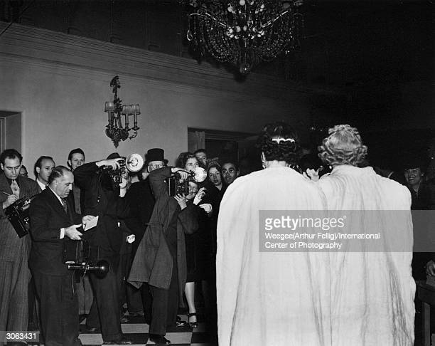 Photographers crowd around the rich and famous in the lobby of the New York Metropolitan Opera on opening night Photo by Weegee/International Center...