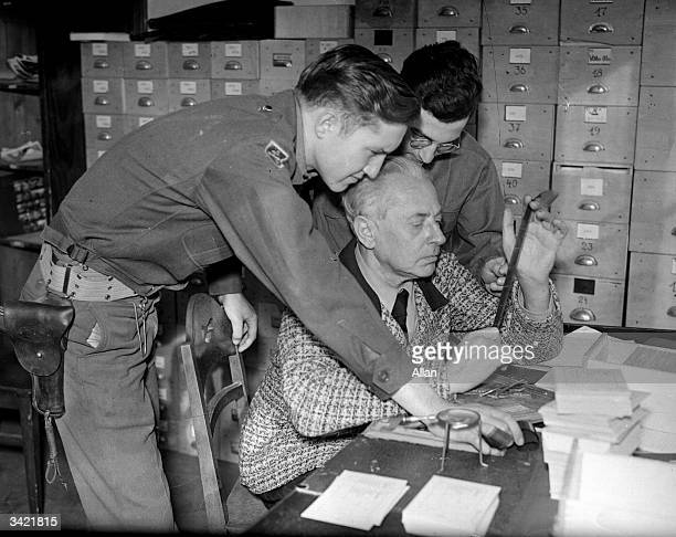 Hitler's photographer Heinrich Hoffmann inspecting evidence during the Nuremberg War Crimes Trial