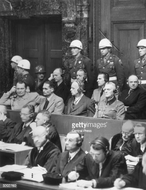 Members of Adolf Hitler's Third Reich sit in the witness box with headsets on during the International Military Tribunal's war crimes trial in...