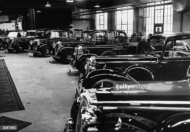 A row of fourteen Daimlers ordered specifically by the South African government for the upcoming Royal Tour of King George VI and Queen Elizabeth The...
