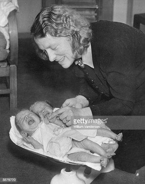 Mrs Kampion weighing her three-month-old twin daughters Anne and Shirley at home in Kingsbury. When they were born they weighed less than...