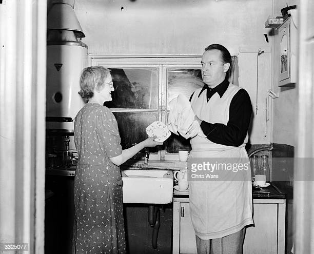 Comedian Bob Hope helps his Aunt Lucy with the washingup after a teaparty at Hitchin Hertfordshire Hope is in Britain to attend the Royal Wedding and...