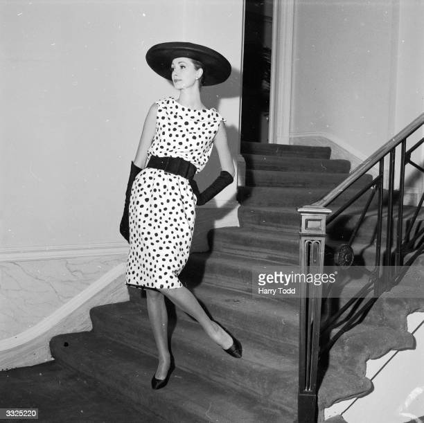Model Barbara Mendoza wearing a black and white spotted cocktail dress calaled 'Pastille' and a 'Cartwheel' black silk hat by Laye at a showing of...