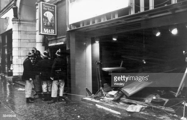 Firemen survey the damage outside the Birmingham pub 'Tavern in the Town' after an IRA bomb blast