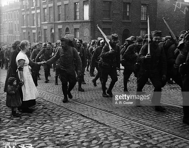 Slum dwellers in Liverpool shake hand with American soldiers who are marching through the streets after disembarkation